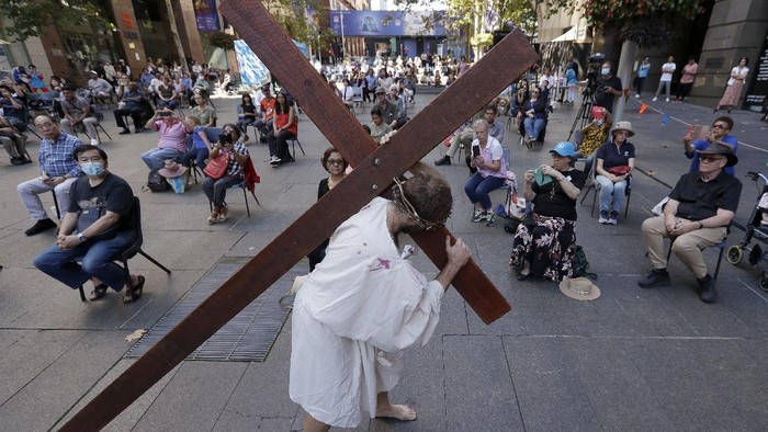 Actor Timothy Watkins carries a cross during his portrayal of Jesus Christ in a reenactment of the Journey to the Cross in Sydney, Australia, Friday, April 2, 2021, during Good Friday observance. Christians around the world are marking the death of Jesus Christ ahead of Easter Sunday. (AP Photo/Rick Rycroft)