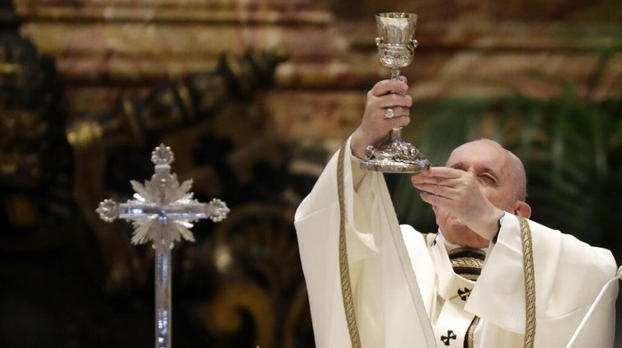Pope Francis blows inside an amphora containing holy oil during a Chrism Mass inside St. Peters Basilica, at the Vatican, Thursday, April 1, 2021. During the Mass the Pontiff blesses a token amount of oil that will be used to administer the sacraments for the year. (AP Photo/Andrew Medichini, pool)