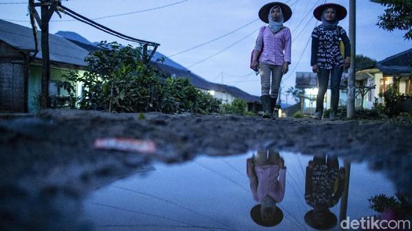 Dua orang warga Desa Tugu Utara, Kab Bogor, Jawa Barat, berjalan menyusuri jalan kampung untuk menuju kebun teh.