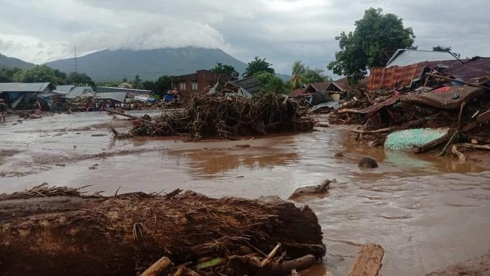 Sejumlah warga menyaksikan rumah yang rusak akibat banjir bandang di Desa Waiburak, Kecamatan Adonara Timur, Flores Timur, NTT, Minggu (4/4/2021). Berdasarkan data BPBD Kabupaten Flores Timur sebanyak 23 warga meninggal dunia akibat banjir bandang yang dipicu hujan dengan intensitas tinggi pada minggu dini hari. ANTARA FOTO/HO/Dok BPBD Flores Timur/wpa/foc.