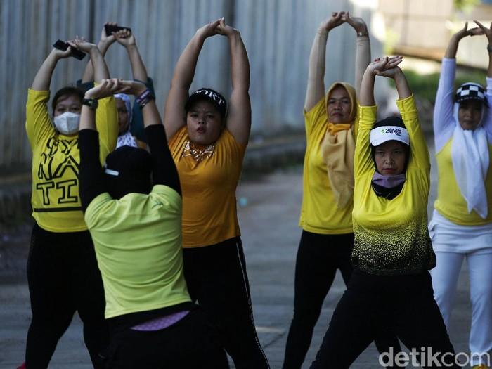 Menjaga kesehatan di masa pandemi Corona, sejumlah emak-emak melakukan senam. Mereka memanfaatkan lahan di kolong jembatan layang tol Becakayu, Jakarta Timur.