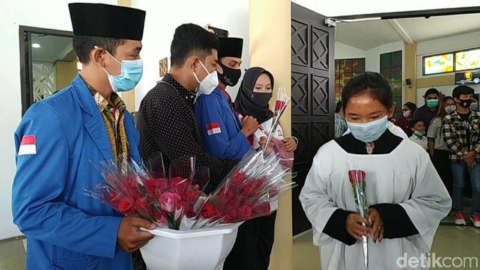 Sejumlah mahasiswa muslim membagikan bunga ke umat kristiani yang tengah merayakan Paskah