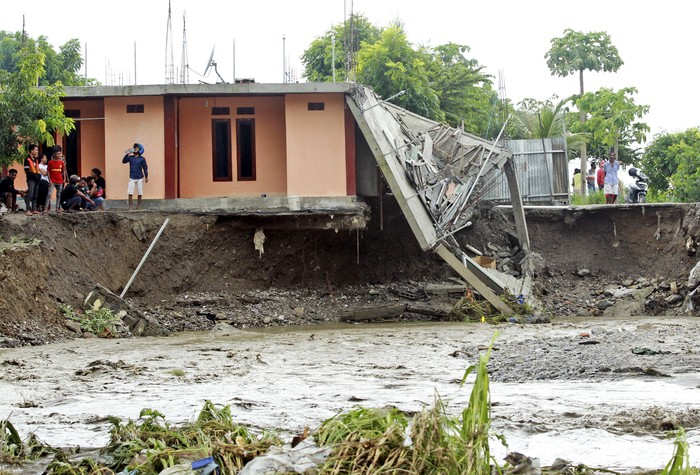 People walk amid debris at a village affected by flood in Ile Ape, on Lembata Island, East Nusa Tenggara province, Indonesia, Sunday, April 4, 2021 photo. Multiple disasters caused by torrential rains in eastern Indonesia have left dozens of people dead or missing while displacing thousands, the countrys disaster relief agency said Monday.