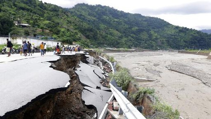 Residents inspect a damaged road following a flood in Dili, East Timor, Monday, April 5, 2021. Multiple disasters caused by torrential rains in eastern Indonesia and neighboring East Timor have left a number of people dead or missing as rescuers were hampered by damaged bridges and roads and a lack of heavy equipment Monday. (AP Photo/Kandhi Barnez)
