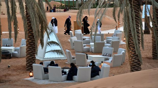 Visitors relax in a lounge area beneath palm trees at the