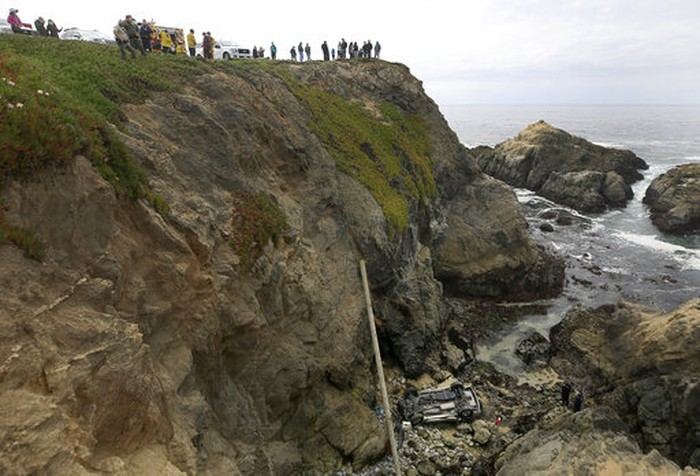 A long line from Sonoma County Sheriff's helicopter Henry 1 is used to safely transport rescue personnel to a beach below after a vehicle plummeted from the Bodega Head parking lot in Bodega Bay, Calif., landing upside down 100 feet below, killing two people in the SUV, Saturday, April 3, 2021. (Kent Porter/The Press Democrat via AP)