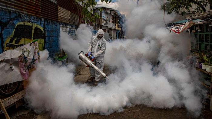 MANILA, PHILIPPINES - A worker wearing a hazmat suit uses a fogging machine to disinfect a street as preventive measure against COVID-19 in Manila, Philippines. Curfews and stricter lockdowns are being implemented in several areas across the Philippines as the country experiences its worst surge in cases since the lockdown began more than a year ago. The country has reported more than 693,000 cases of COVID-19 so far, with at least 13,095 deaths. (Photo by Ezra Acayan/Getty Images)