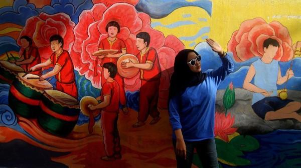 Seorang berfoto di depan lukisan mural di dinding rumah toko di Gajahmada 9, Pontianak, Kalimantan Barat, Selasa (6/4/2021).