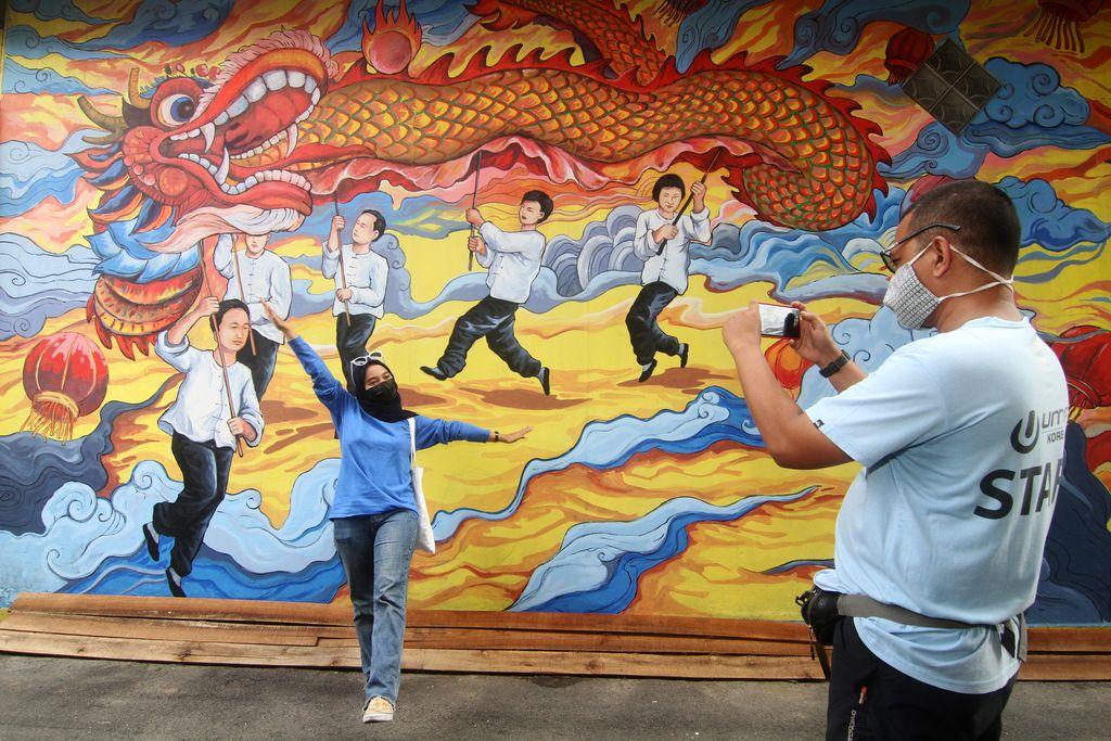 Seorang warga berpose di depan lukisan mural di dinding rumah toko di Gajahmada 9, Pontianak, Kalimantan Barat, Selasa (6/4/2021). Mural yang menggambarkan kesenian Tionghoa dan diinisiasi oleh pegiat seni Hervin Yulianto tersebut menjadi salah satu destinasi wisata baru di Kota Pontianak. ANTARA FOTO/Jessica Helena Wuysang/wsj.