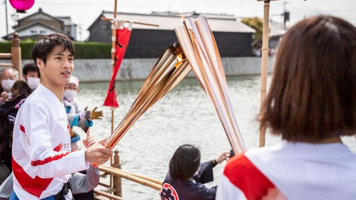 HANDA, JAPAN - APRIL 06: A torch bearer holds the torch on the boat called 'Chintoro boat', used in a local festival dating back to the Edo Period during the Tokyo Olympic Games Torch Relay on April 06, 2021 in Handa, Aichi, Japan. (Photo by Yuichi Yamazaki/Getty Images)