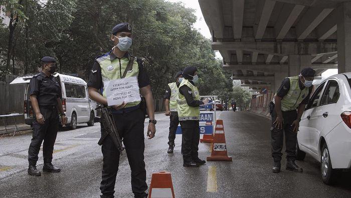 KUALA LUMPUR, MALAYSIA - MARCH 21: Members of Malaysian Royal Police Force check on vehicles at a road block in a residential neighbourhood on March 21, 2020 in Kuala Lumpur, Malaysia. Malaysian police have set up more than 500 roadblocks as Malaysias lockdown enters its 4th day. The measures were introduced in an attempt to stop the spread of coronavirus (COVID-19). (Photo by Rahman Roslan/Getty Images)