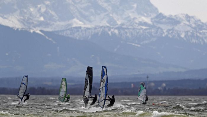 Surfers brave high winds to speed on the waves at lake Ammersee in front of the Alps near Herrsching, Germany, Monday, April 5, 2021. (AP Photo/Matthias Schrader)