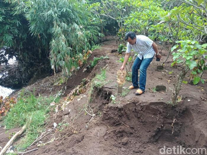 Sungai Pancir Gunting menggerus makam di Dusun Betek Utara, Desa Betek, Kecamatan Mojoagung, Jombang. Warga setempat memindah sejumlah kuburan yang posisinya kritis.
