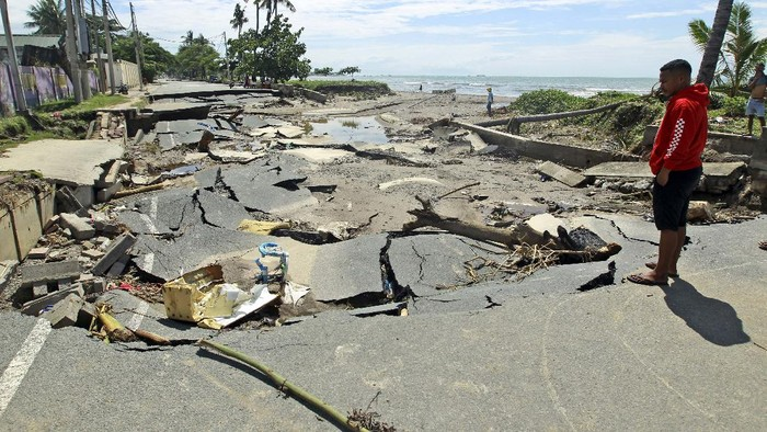 A woman walks along a road damaged by major flooding in Dili, East Timor, Tuesday, April 6, 2021. Several disasters brought on by severe weather in eastern Indonesia and neighboring East Timor have left a number of people dead or missing. (AP Photo/Kandhi Barnez)