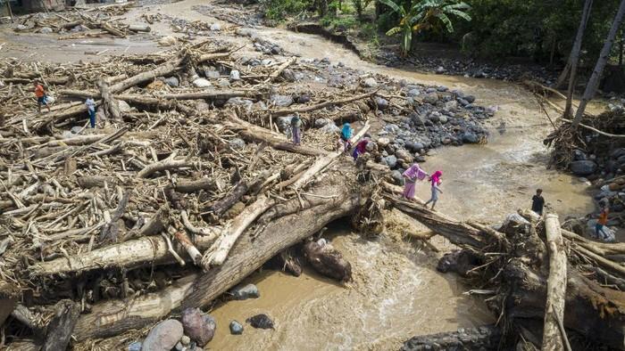 Warga melewati tumpukan kayu-kayu yang menyumbat dan merusak salah satu jembatan penghubung antardesa di Adonara Timur, Kabupaten Flores Timur, Nusa Tenggara Timur (NTT), Rabu (7/4/2021). Menurut Organisasi Wahana Lingkungan Hidup Indonesia (Walhi), banjir bandang dan tanah longsor yang melanda di sejumlah wilayah di NTT dipicu kerusakan lingkungan akibat alih fungsi lahan, pertambangan, dan pembalakan liar. ANTARA FOTO/Aditya Pradana Putra/hp.