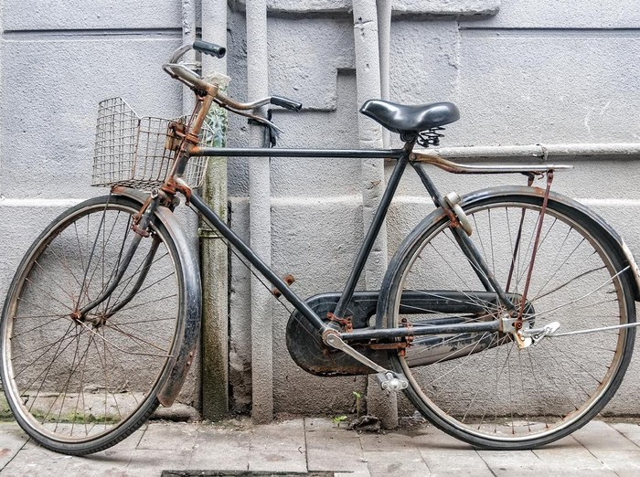 Old and rusty bicycle parked against a gray city wall