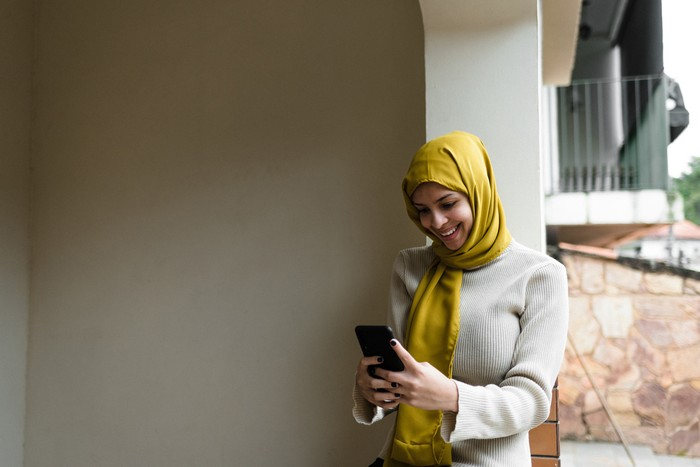 Young woman, cloth on her head, on the phone, working, looking at Ramadan, religious dress