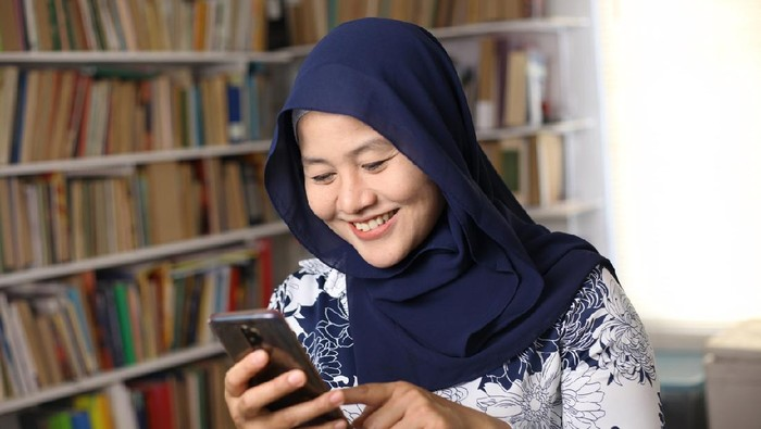 Asian muslim woman using phone and smiling. Feeling happy. Female doing communication on her smart phone, sending message or browsing online
