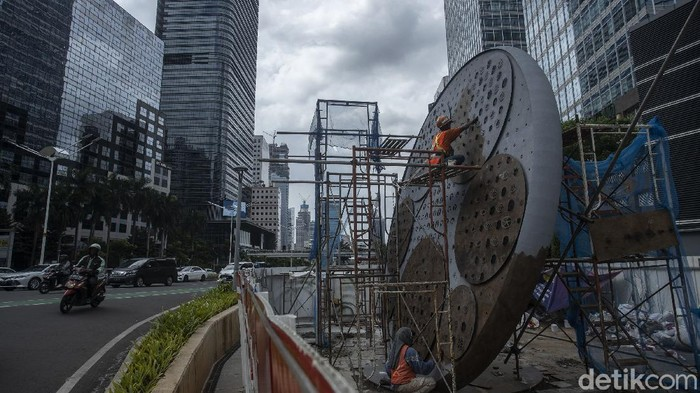 Pekerja menyelesaikan pembangunan Tugu Sepeda di Jalan Jenderal Sudirman, Jakarta, Senin (7/4/2021).   Pembangunan tugu yang berbentuk satu buah ban sepeda berukuran raksasa tersebut sebagai pengingat momentum penggunaan sepeda yang masif digunakan masyarakat Ibu Kota di tengah pandemi COVID-19.