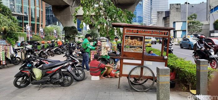 Trotoar di Kuningan, Jakarta Selatan, selain jadi tempat putar balik pemotor juga menjadi tempat berjualan. 7 April 2021. (Rahmat Fathan/detikcom)