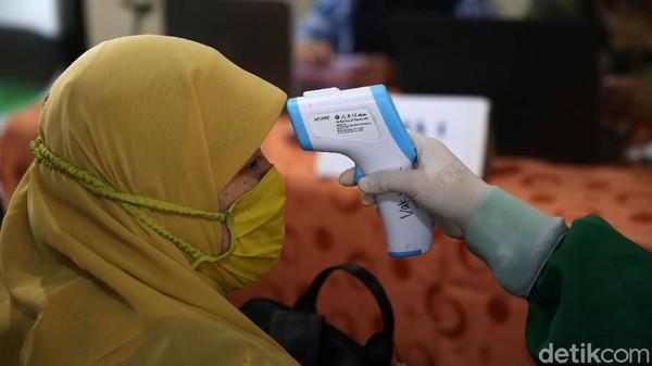 Para guru dicek suhu tubuhnya sebelum mengikuti vaksinasi COVID-19.