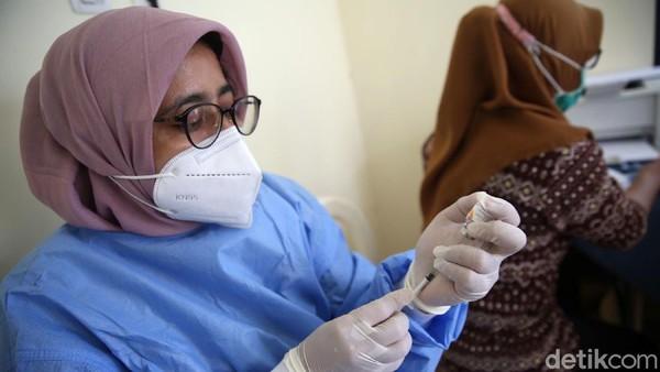 Petugas kesehatan bersiap memberikan suntikan vaksin kepada tenaga pengajar atau guru.