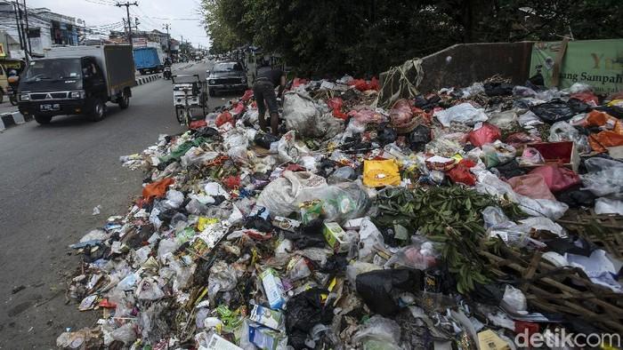 Pengendara melintas di Jalan Maulana Hasanudin, Batu Ceper, Tangerang, Kamis (8/4/2021). Sampah yang menumpuk kini mulai merambat ke jalan.