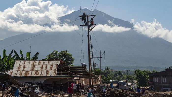 Sejumlah petugas memperbaiki jaringan listrik yang terputus akibat banjir bandang di Adonara Timur, Kabupaten Flores Timur, Nusa Tenggara Timur (NTT), Kamis (8/4/2021). Pemulihan infrastruktur dilakukan untuk kembali menghidupkan perekonomian masyarakat setempat pascabencana alam yang terjadi pada Minggu (4/4) tersebut. ANTARA FOTO/Aditya Pradana Putra/rwa.