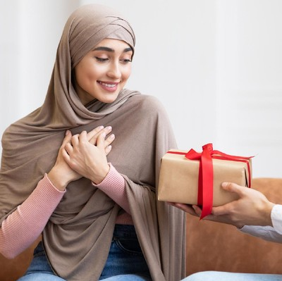 Valentines Day. Arab Man Surprising Wife With A Gift Giving Wrapped Present Box To Her Sitting On Couch At Home. Birthday Holiday Celebration, Romantic Presents And Gifts. Panorama