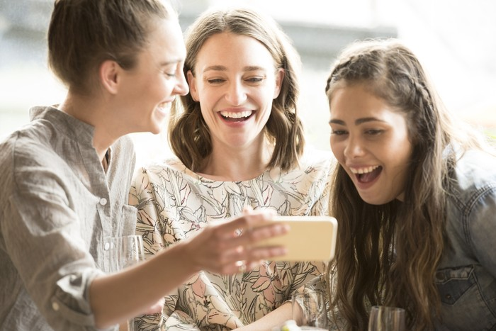 Three women looking at smartphone, smiling and laughing. Three female friends using social media, having fun, togetherness