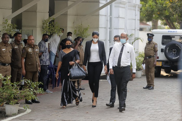 Mrs. World 2019 Caroline Jurie, center, leaves a police station after obtaining bail in Colombo, Sri Lanka, Thursday, April 8, 2021. Juries decision to remove the crown from the the winning Mrs. Sri Lanka contestant on stage moments after the winner was announced, because of claims she was a divorcee, drew widespread social media condemnation.  The winner Pushpika de Silva who was crowned again later had complained to police that her head was wounded when the clips of her crown were removed by Jurie. (AP Photo/Eranga Jayawardena)