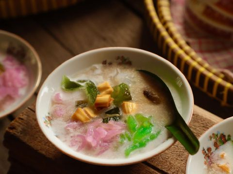 Es Dawet, or also popularly known as Es Cendol, a Javanese icy dessert of rice noodle jelly in coconut milk soup sweetened with coconut brown sugar that has been infused with jackfruit. In this version, the rice noodle is made into three colors instead of just the usual green one. Then cooling green grass jelly is also added to the mixture. The dish is served in old-fashioned ceramic bowls.