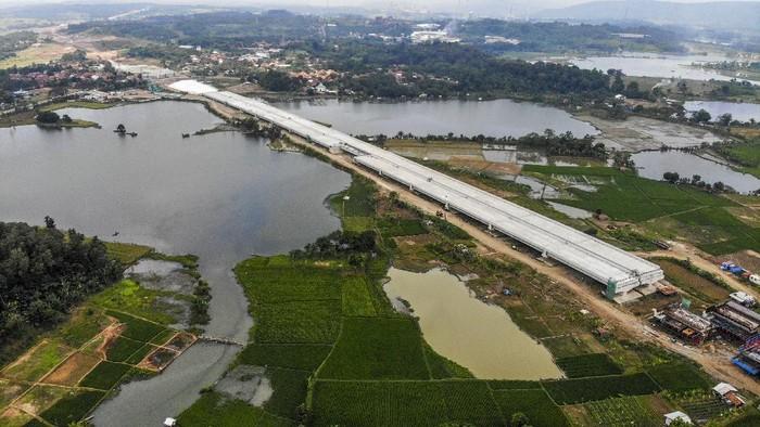 Foto udara proyek pembangunan Jalan Tol Jakarta - Cikampek (Japek) II Selatan di Karawang, Jawa Barat, Sabtu (10/4/2021). Kementerian Pekerjaan Umum dan Perumahan Rakyat (PUPR) bersama PT Jasamarga Jakarta Cikampek Selatan menyatakan progres pembangunan konstruksi jalan tol Japek II Selatan seksi 3 Taman Mekar - Sadang sepanjang 27,85 Km telah mencapai 42,58 persen yang ditargetkan rampung pada Maret 2022. ANTARA FOTO/M Ibnu Chazar/wsj.