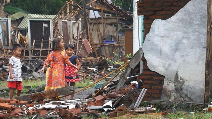 Seorang warga menelepon di depan rumahnya yang hancur akibat gempa di Majangtengah, Malang, Jawa Timur, Minggu (11/4/2021). Badan Nasional Penanggulangan Bencana (BNPB) melaporkan sedikitnya 1.189 unit rumah rusak akibat gempa bermagnitudo 6,1 yang mengguncang kawasan Malang dan sekitarnya. ANTARA FOTO/Ari Bowo Sucipto/rwa.