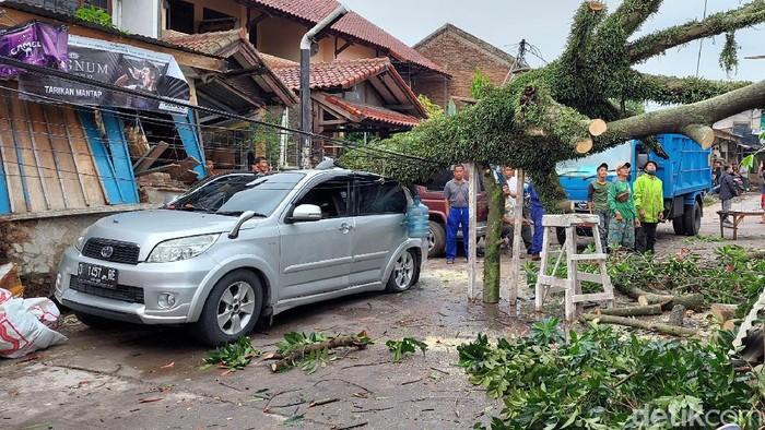 Mobil rusak tertimpa pohon tumbang di Bandung.