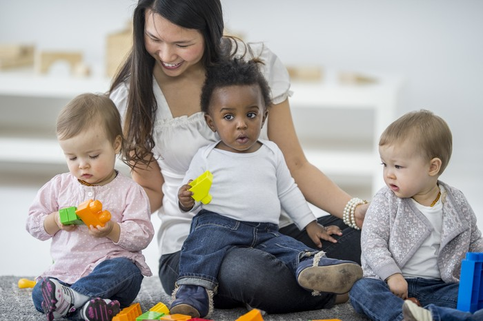 A group of babies are sitting with their babysitter on the carpet. The babies are playing with colorful toy blocks.