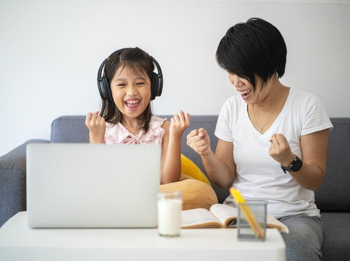 Asian girl and her teacher using laptop for online study during homeschooling at home during Coronavirus or Covid-19 virus outbreak situation