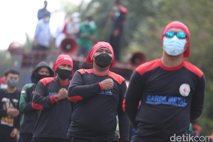 Sejumlah buruh melakukan aksi unjuk rasa di Patung Kuda, Monas, Jakarta, Senin (12/4/2021).  Puluhan buruh yang tergabung dalam Konfederasi Serikat Pekerja Indonesia (KSPI) hari ini menggelar aksi untuk menyampaikan tuntutan di patung kuda dan Mahkamah Konstitusi (MK).