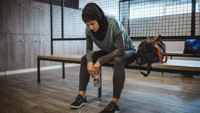 Young woman in dressing room after hard training in gym. Wearing sports clothing and hijab.