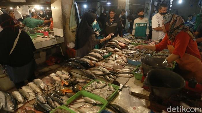 Pedagang ikan segar tengah melayani pembeli di pasar tradisional Pondok Gede, Kota Bekasi, Senin (12/04/2021).
