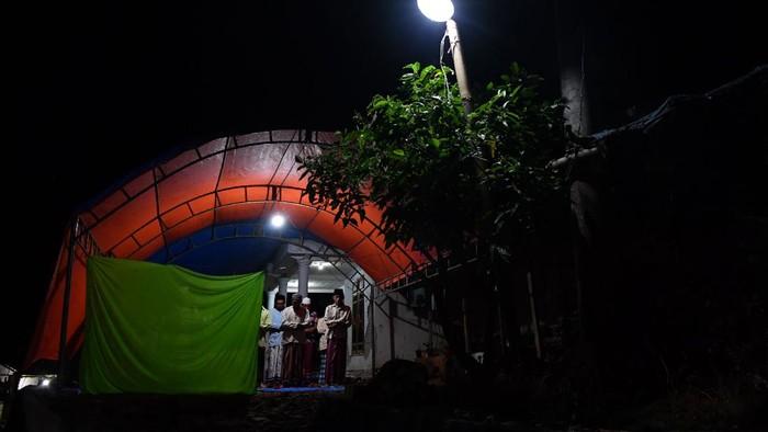 Warga melaksanakan shalat tarawih pertama di Desa Kaliuling, Lumajang, Jawa Timur,  Senin (12/4/2021). Shalat tarawih tersebut dilaksanakan di tenda darurat yang dibangun warga di halaman rumahnya yang rusak akibat gempa pada Sabtu (10/4). ANTARA FOTO/Zabur Karuru/foc.