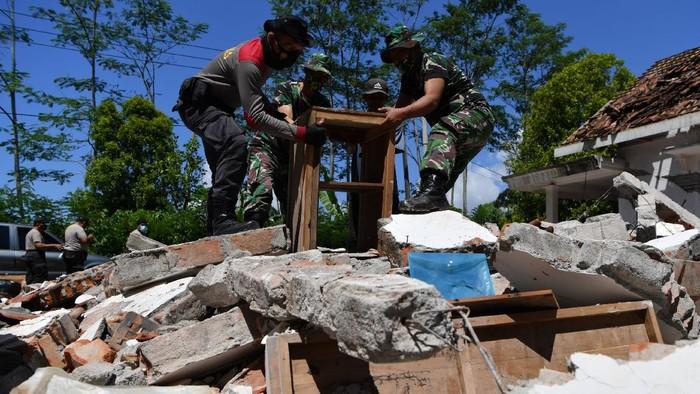Sejumlah prajurit TNI AD membantu warga membersihkan puing-puing bangunan yang rusak akibat gempa di Desa Kaliuling, Lumajang, Jawa Timur,  Senin (12/4/2021). Personel TNI dan Polri dikerahkan untuk membantu warga korban gempa untuk membersihkan sisa-sisa puing bangunan yang rusak akibat gempa. ANTARA FOTO/Zabur Karuru/foc.