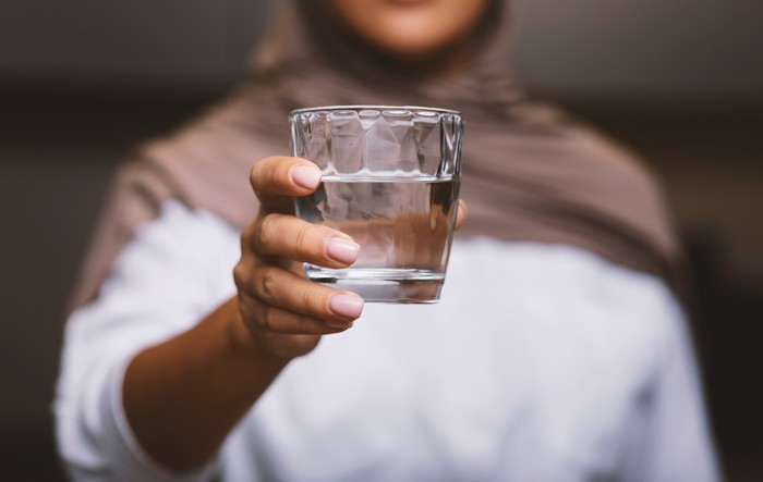 Unrecognizable Muslim Woman Offering Glass Of Water To Camera Standing In Modern Kitchen At Home, Wearing Hijab. Healthy Hydration, Drink More Water And Stay Hydrated. Selective Focus, Cropped