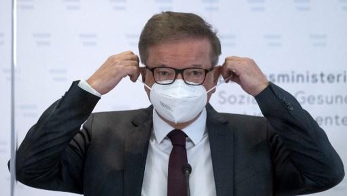 Austrias Health Minister Rudolf Anschober takes off his face mask as he arrives to address a press conference on April 13, 2021 in Vienna, amid the novel coronavirus / COVID-19 pandemic. - Anschober announced that he would resign, saying managing the coronavirus crisis had overworked him. (Photo by JOE KLAMAR / AFP)