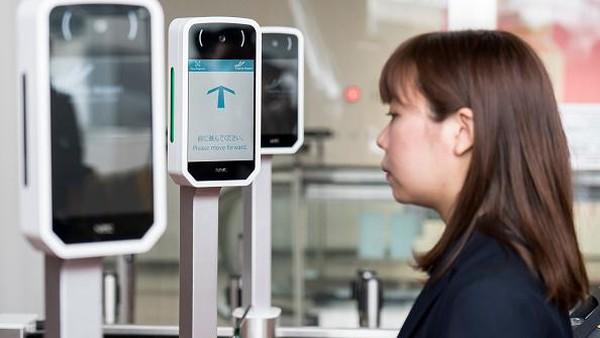 Seorang pegawai mendemonstrasikan penggunaan teknologi pengenalan wajah Face Express yang mulai diujicoba di Bandara Internasional Narita, Jepang, Selasa (13/4/2021).