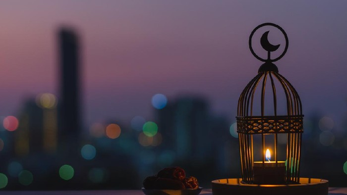 Lantern that have moon symbol on top and small plate of dates fruit with dusk sky and city bokeh light background for the Muslim feast of the holy month of Ramadan Kareem.