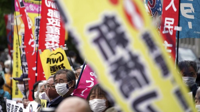People protest against government's decision to start releasing massive amounts of treated radioactive water from the wrecked Fukushima nuclear plant into the sea, during a rally outside the prime minister's office in Tokyo Tuesday, April 13, 2021. The decision, long speculated but delayed for years due to safety concerns and protests, came at a meeting of Cabinet ministers who endorsed the ocean release as the best option.  Signs mean