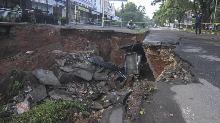 Sejumlah warga melihat jalan yang longsor di Jalan Raya Boulevard, GDC, Depok, Jawa Barat, Selasa (13/4/2021). Longsor yang terjadi pada Senin (12/4) pukul 21.00 WIB tersebut akibat intensitas hujan yang tinggi  dan menyebabkan sebagain jalan amblas dengan kedalaman dan lebar kurang lebih 5 meter. ANTARA FOTO/Asprilla Dwi Adha/hp.