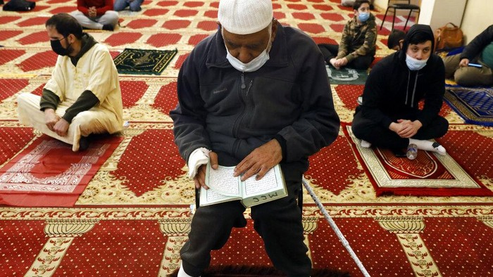 A Muslim makes a donation after an evening prayer called