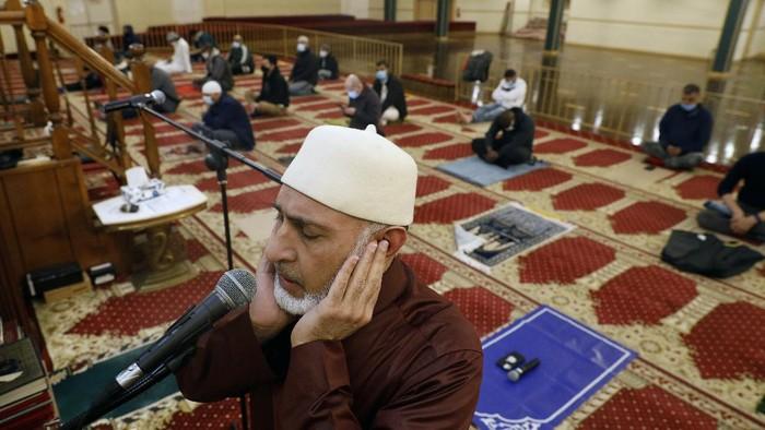 A Muslim makes a donation after an evening prayer called